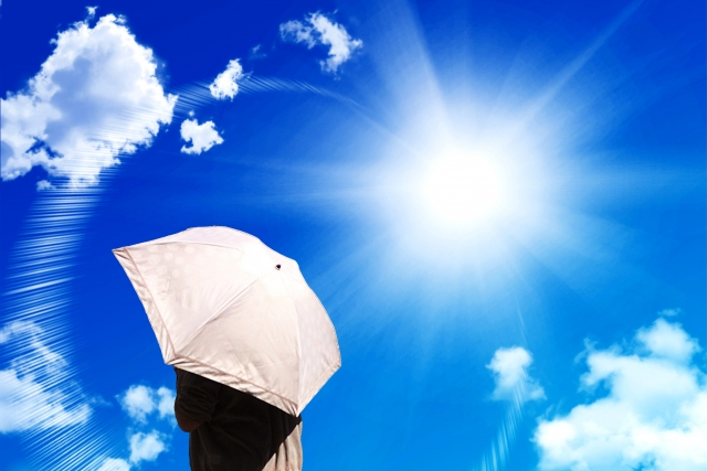 夏の日差しと日傘をさす女性